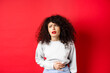 Leinwandbild Motiv Woman feeling sick, bending and touching belly, having stomach ache or menstrual cramps, standing on red background