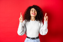 Hopeful And Positive Woman With Red Lips And Curly Hair, Cross Fingers For Good Luck And Making Wish, Praying For Dream Come True, Smiling Excited, Red Background