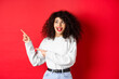 Leinwandbild Motiv Excited pretty girl with curly hair and red lips, looking and pointing fingers left with amazed face, showing banner, standing on studio background