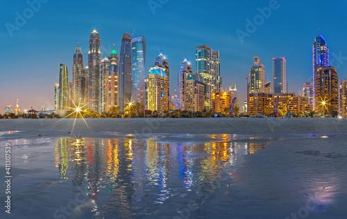 Fototapeta DUBAI, UAE - MARCH 28, 2017: The evening skyline of Marina towers from beach
