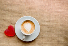 One White Cup On A Saucer With  Coffee And Marmalade Heart Stands On A Windowsill On Burlap Fabric, Loneliness.  Drink With Milk, With Foam Heart, Top View.