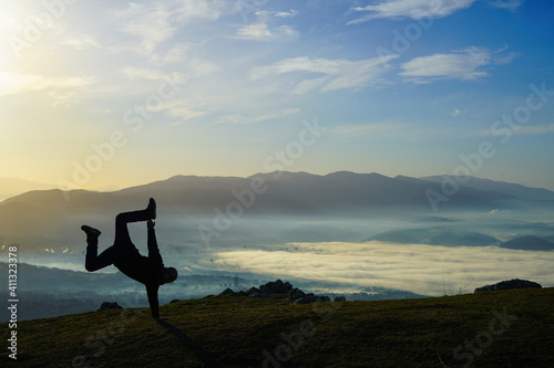 Fototapeta Breakdancer on the top of the mountain during the sunrise with fog on the valley