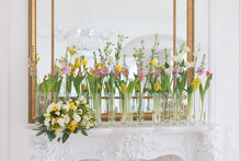 Elegant Spring White, Pink And Yellow Wedding Decor Of Daffodils, Lisianthus, Tulips And Hyacinth In Plain Transparent Glass Vases On A Vintage Fireplace