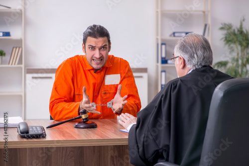 Fotografía Old male judge meeting with young captive in courthouse