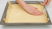 Using A Plastic Wrap Chef  Unfurl Pizza Dough Onto A Baking Pan. Close Up Step By Step Homemade Pizza Recipe