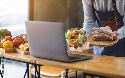 Obraz A woman videoblogger cooking and filming salad and sandwich in the kitchen, online learning cooking class concept - fototapety do salonu