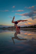 Yoga Inversion Pose On A Beach At Low Tide
