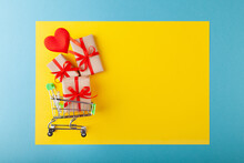 Red Heart, Gift Box With Red Ribbon Inside Mini Grocery Cart On Colored Background