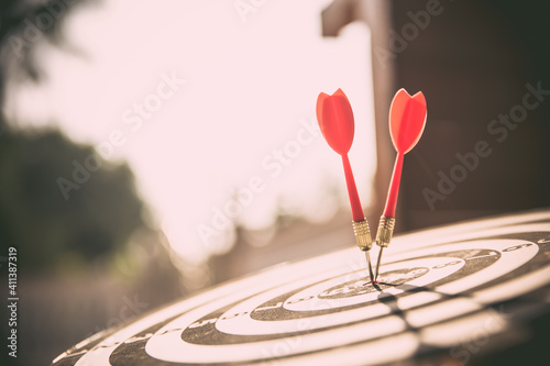 Obraz Close-up the bullseye target or dart board has red dart arrow throw hitting the center of a shooting with the sun shines and shadows for business targeting and winning goals business concepts - fototapety do salonu