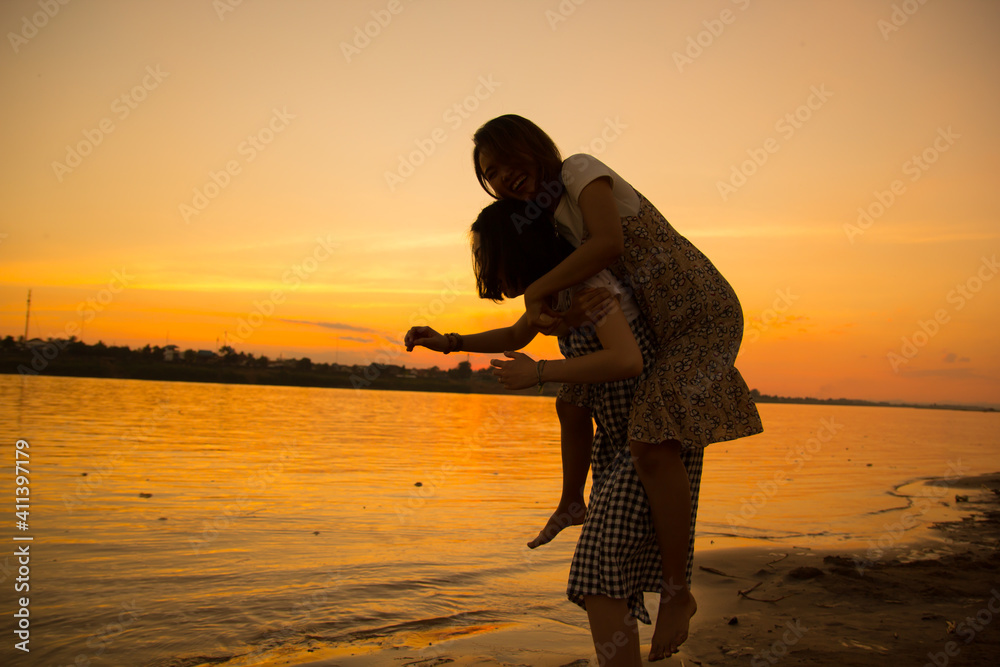 Fototapeta Woman Piggybacking Friend While Standing At Beach Against Sky During Sunset
