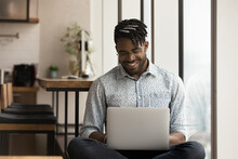 Skilled African Man Freelancer Sit In Comfortable Pose Work From Home Consult Client By Video Link Write Programme Code On Pc. Young Black Guy Relax At Home With Laptop Post Comments At Social Network