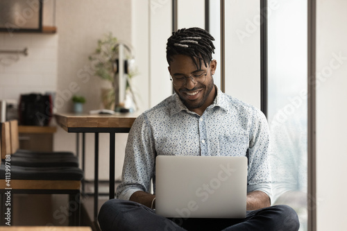 Fotografie, Obraz Skilled african man freelancer sit in comfortable pose work from home consult client by video link write programme code on pc