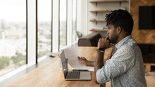 Concentrated Young African Man Read Printed Document Before Laptop Screen Compare Data Think On Text Edit Check Errors. Thoughtful Black Male Analyse Financial Report Plan Changes In Contract Project