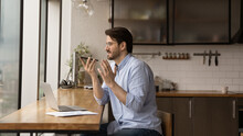 Inspired Male Remote Worker Sit At Home Office In Kitchen Before Laptop Pc Dictate Audio Message Via Voice App On Cell. Young Man Freelancer Ask Mobile Phone Ai Assistant To Search Information Online