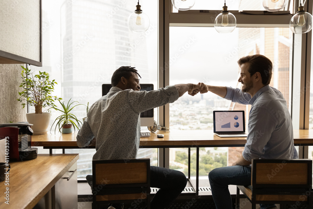 Fototapeta Well done, buddy. Motivated diverse young men coworkers bump fists on workplace feel excited achieve common goal. Two workers international business team members share success glad to help one another