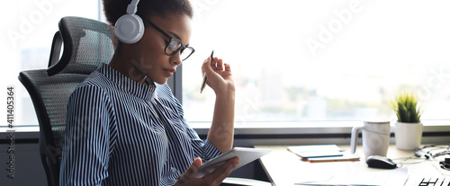 Obraz Beautiful african american woman is working using digital tablet while sitting in creative office. - fototapety do salonu