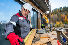 Builder Man Is Processing Wood. Carpenter Processes Boards With A Circular Saw. Carpenter On Background Of A House Under Construction. He Cuts Wood Beams With A Stationary Circular Saw.