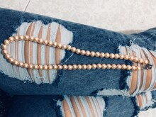 Midsection Of Woman Wearing Torn Jeans With Pearl Necklace