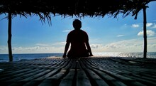 Rear View Of Silhouette Man Sitting In Gazebo At Beach Against Blue Sky