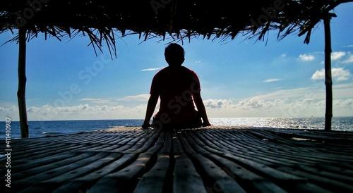 Fotografie, Obraz Rear View Of Silhouette Man Sitting In Gazebo At Beach Against Blue Sky