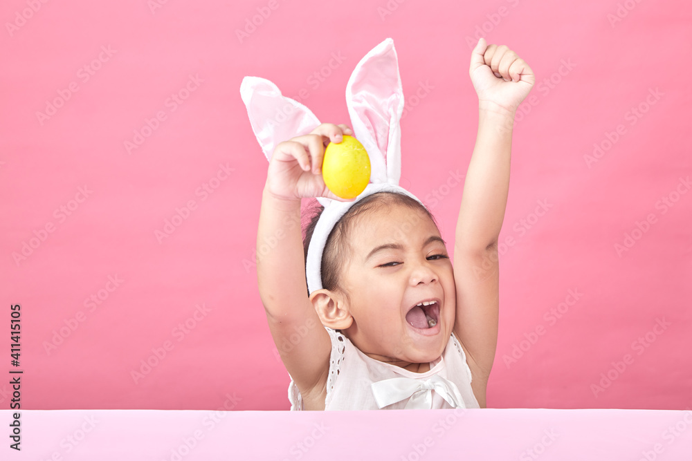 Fototapeta Cheerful Girl With Arms Raised Holding Easter Egg Sitting Against Pink Wall