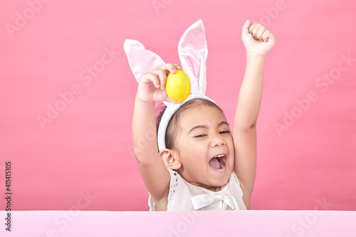 Fotografie, Obraz Cheerful Girl With Arms Raised Holding Easter Egg Sitting Against Pink Wall