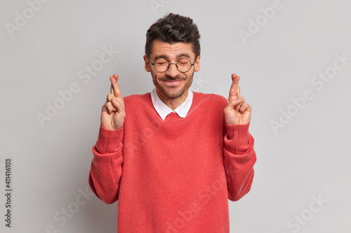 Fototapeta Positive happy man closes eyes believes dreams come true hopes to get promotion at work crosses fingers dressed in casual red jumper isolated over grey background