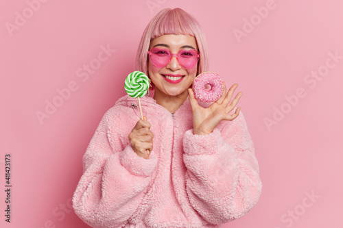 Canvas Pleased young Asian woman with pink bob hair smiles gently holds lollipop and delicious doughnut wears trendy heart shaped sunglasses fur coat poses indoor has sweet tooth enjoys spare time