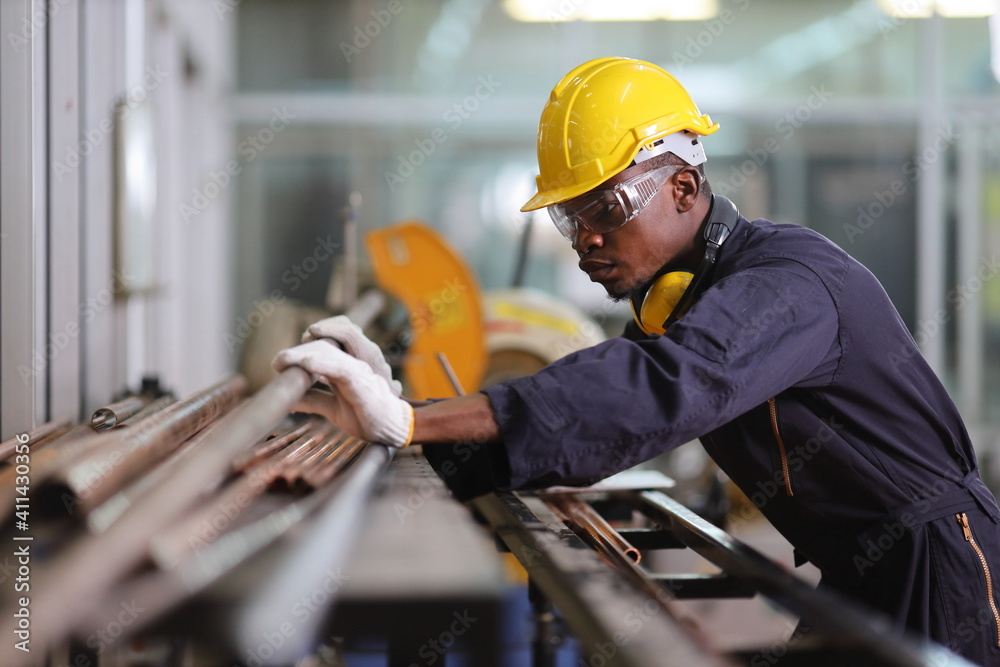 Fototapeta African American mechanic engineer worker is choosing copper tube for sawing while working in coolant factory with copy space