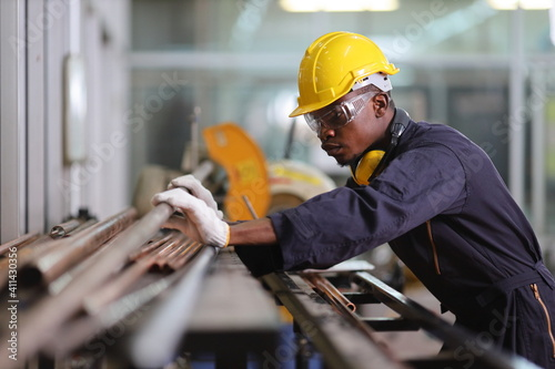 Fototapeta African American mechanic engineer worker is choosing copper tube for sawing whi