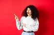 Leinwandbild Motiv Surprised attractive girl with curly hair, pointing and looking aside at empty space, showing logo or advertisement, standing on red background