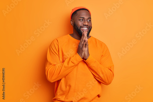 Tela Positive dark skinned bearded man smiles happily keeps palms together has belief in better wears casual long sleeved jumper and hat poses against vivid orange background