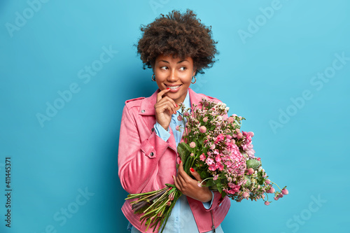 Slika na platnu Horizontal shot of dreamy ethnic woman looks happily aside hholds bouquet of flowers wears fashionable jacket comes on date with lover isolated over blue background