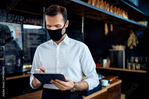 Obraz Waiter restaurant owner wearing mask using digital tablet - fototapety do salonu