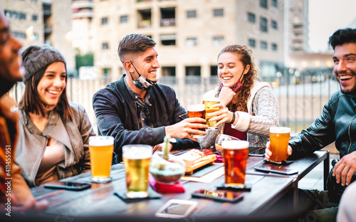 Obraz na plátně Young friends drinking beer with open face mask - New normal lifestyle concept w