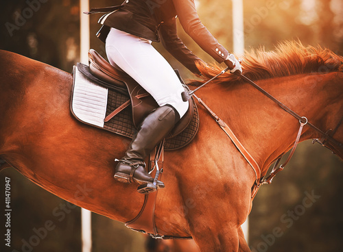 A sorrel horse with a beautiful red mane and a rider in the saddle jumps high, illuminated by the sunlight Fototapet