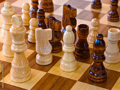 black and white wooden pieces on a chessboard Fototapeta