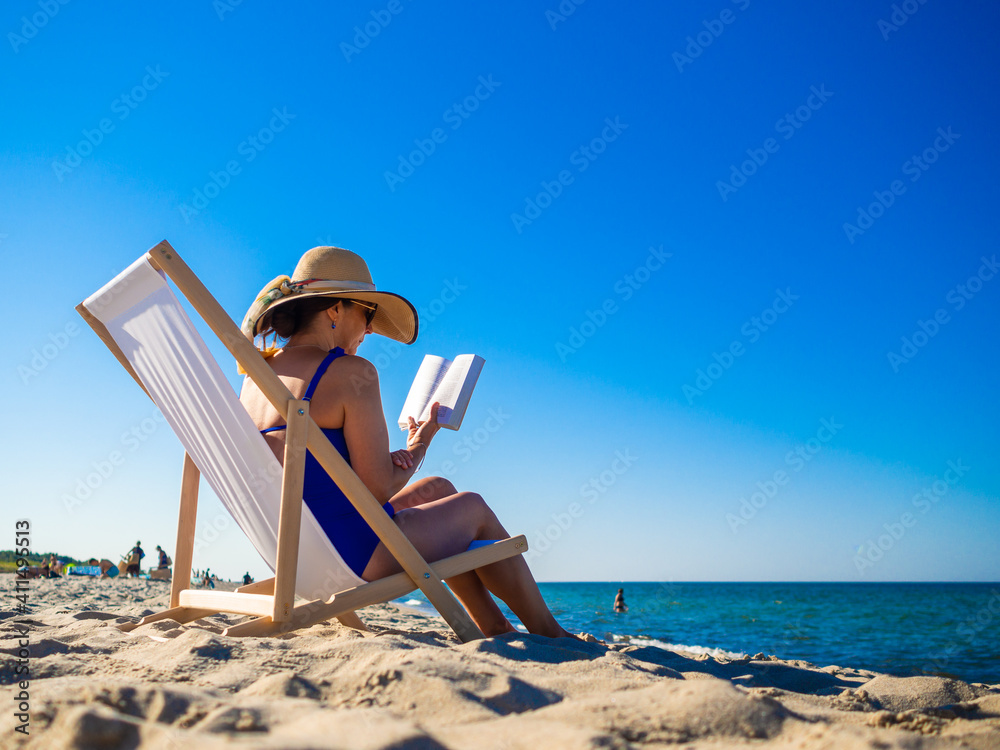 Fototapeta Woman relaxing on beach reading book sitting on sunbed