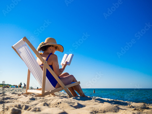 Obraz Woman relaxing on beach reading book sitting on sunbed  - fototapety do salonu
