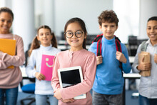 Smiling Asian Girl Holding Tablet Standing With Classmates