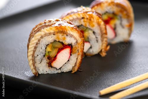Fototapeta Sushi roll with rice, crab, cucumber, avocado ,tobiko, eel. Sushi menu. Japanese food. obraz