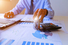 Midsection Of Businessman Holding Money Roll By Calculator And Laptop At Office Desk