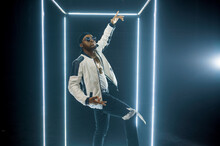 Rapper In Sunglasses Poses In Illuminated Cube