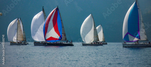 Obraz na plátně sail boat yacht race regatta with multi colorful spinnaker sails and mountain ba