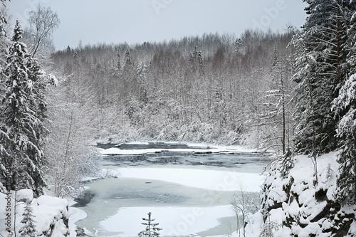 Landscape with a frozen river in the middle of a snow covered forest © Alexey Kuznetsov