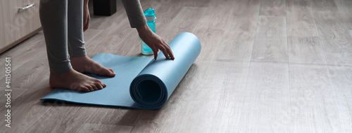 Obraz Teenage girl doing fitness exercise, practicing yoga at home. Healthy lifestyle concept. She spreads the yoga mat. Workout at home. Home interior, daytime. - fototapety do salonu