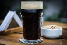 Black Porter Stout Bock Beer With Foam In Pint Glass With Peanuts On A Wooden Table