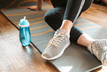 Woman Sits On Yoga Mat Rolled On The Floor And Drinks Water From Bottle Resting After Home Fitness Class, Sport, Active Lifestyle Concept