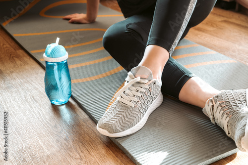 Obraz Woman sits on yoga mat rolled on the floor and drinks water from bottle resting after home fitness class, sport, active lifestyle concept - fototapety do salonu