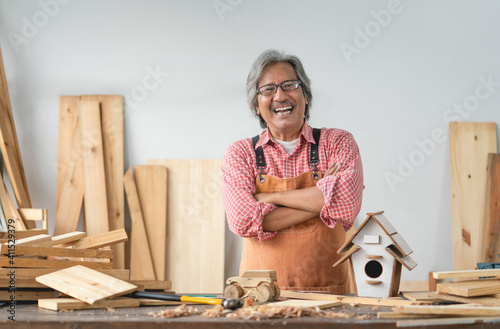 Obraz Asian senior carpenter man with crossed arms smile at home carpentry workshop - fototapety do salonu